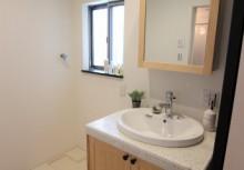 洗面 キッチンと同仕様の無垢材を採用。さらに、天板を高品質美濃焼タイルで美しい質感を活かしたカウンターが豊かな表情を彩ります。鏡を開いてもらうと、そこにも収納できるスペースがあります。