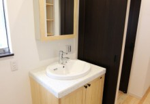 洗面化粧台 キッチンと同仕様の無垢材を採用。さらに、天板を高品質美濃焼タイルで美しい質感を活かしたカウンターが豊かな表情を彩ります。鏡を開いてもらうと、そこにも収納できるスペースがあります。
